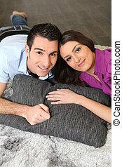a couple lying on a carpet
