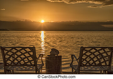 A couple of deck chairs at sunrise on the sea beach.
