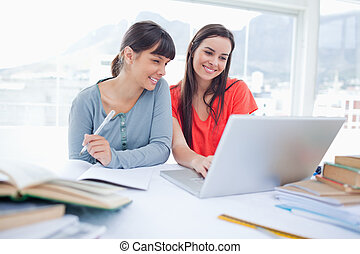 A couple of girls sitting together as they work on the laptop