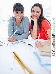 A couple of girls smiling as they look at the camera while doing some homework