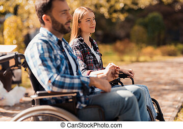A couple of invalids on wheelchairs met in the park. A man and a woman are sitting on shore of the lake holding hands.