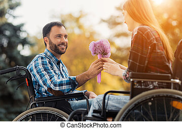 A couple of invalids on wheelchairs met in the park. A man is giving a bouquet of flowers to a woman.