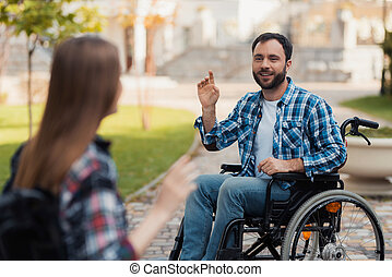 A couple of invalids on wheelchairs met in the park. A man is greeting a woman.