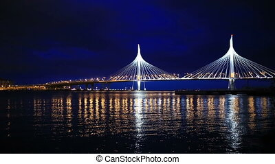 A couple of man and woman watching the night city. At night, the lights of the city flicker on the water. Cable-stayed bridge over the river