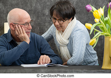 couple of senior reading a book at home