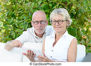 a couple of seniors looking at digital tablet