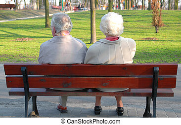 A couple of seniors sitting on a bench in the park, light ...