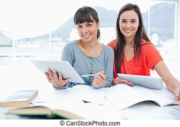A couple of smiling students with tablets in their hands as they both look into the camera