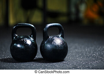 A couple of steel black kettlebells on a blurred background. A kettlebell on a gym floor. Workout. Copy space.