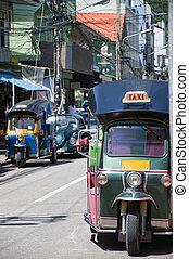 Thai tuk tuks - A couple of Thai tuk tuks sit parked...