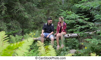 A couple of tourists rest in the woods sitting on a fallen tree