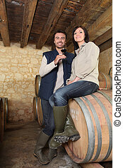 a couple of wine producers in a cellar