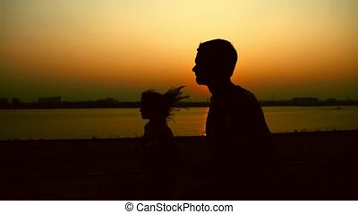 A couple of young adult athletes: woman and man running along promenade of river at sunset, silhouette, slow-motion