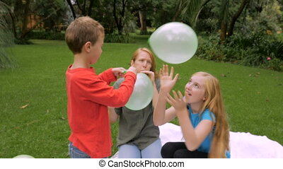 A couple of young kids start hitting a balloon around with their family - slowmo