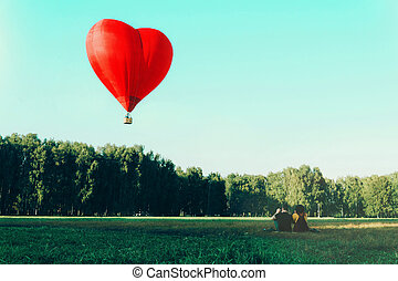 A couple of young people looking at red hot air balloon in shape of heart.
