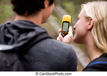 A couple outdoors in the forest using a GPS. Sharp focus on the GPS device.