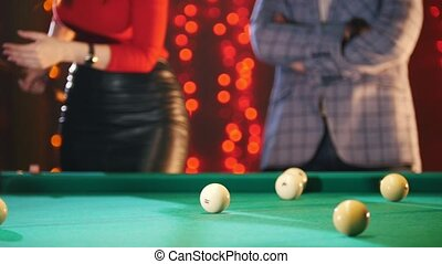 A couple playing billiards. A woman aiming and hit the ball....