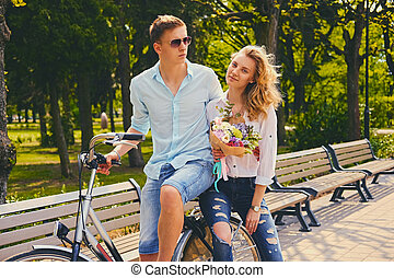 A couple riding on the bicycle in a park.