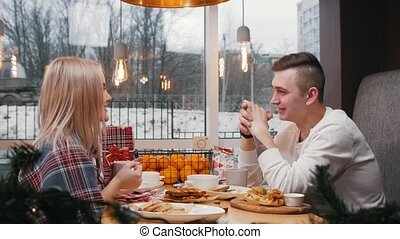 A couple sitting in cafe and talking to each other
