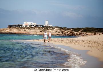 A couple stroll along the shore of the beach