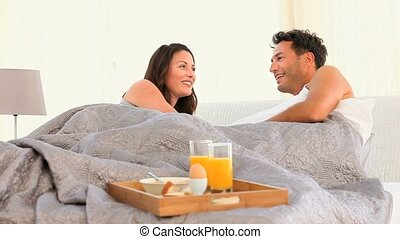 A couple talking to each other in their bed at home