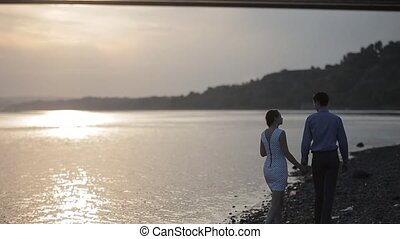 a couple walks a ratio of the river at sunset