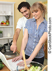 a couple watching a computer in the kitchen