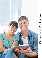 A couple with a tablet pc in their hands smiling as they look into the camera