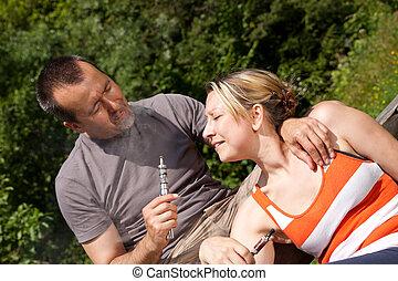 couple with e-cigarette in nature