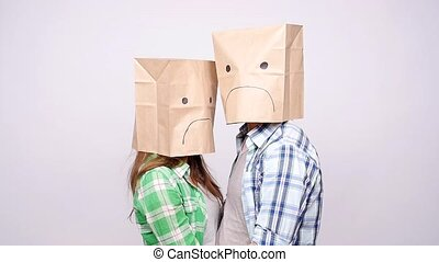 A couple with sad faces with paper bags on their heads on a...