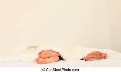A couples feet in the bedroom