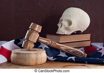 A court hammer and a skull on the background of the flag of the United States,