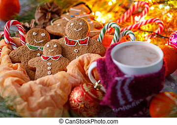 A cozy Christmas evening. A cup of hot cocoa with a small funny scarf and delicious ginger biscuits against the background of fir branches and brilliant lights of garlands.