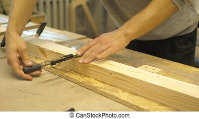 A craftsman in a carpentry workshop clamps wooden planks ...