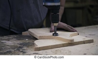 A craftsman is sawing a wooden bar using a hole saw.