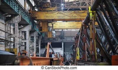A crane is operating in the factory in the distance - the...