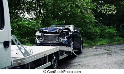 A crashed car being put on a tow truck after an accident....