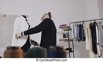A creative tailor or fashion designer makes measurements of a white jacket on a dummy in his studio for sewing clothes. The tailor is measuring clothes pinned to tailoring dummy with measure-tape