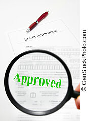 a credit application and magnifying glass with Approved text