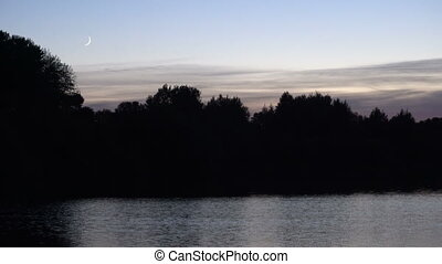 A crescent moon over Lake at dusk, with silhouetted, forest...
