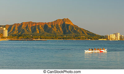 boys paddle an outrigger canoe at waikiki beach with diamond head in the distance
