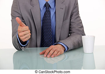 A cropped picture of a businessman giving the thumb up.