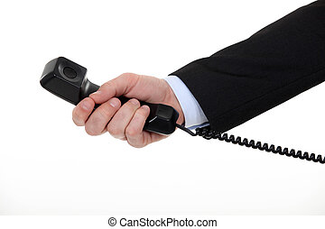 A cropped picture of a businessman holding landline phone.