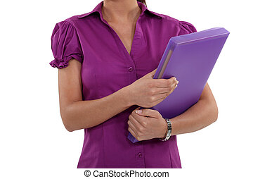 A cropped picture of a businesswoman holding a folder.