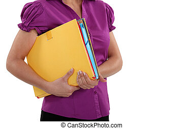 A cropped picture of a businesswoman holding  a file.