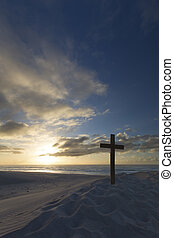 A cross on sand dune next to the ocean with a calm sunrise