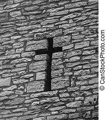 A cross shaped hole in an old brick wall