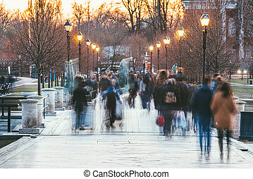 A crowd of blurred people walking in the autumn Park