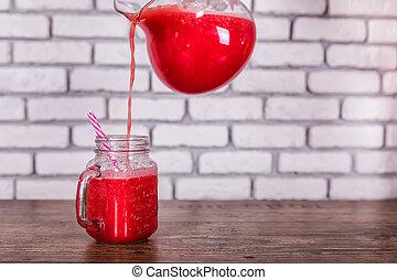 a, cruche, verser, fraîchement, mélangé, fruit rouge, smoothie, dans, pot verre, à, paille