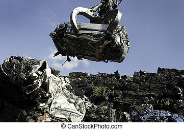 A crushed car being lifted on to pile of other crushed cars in scrap yard
